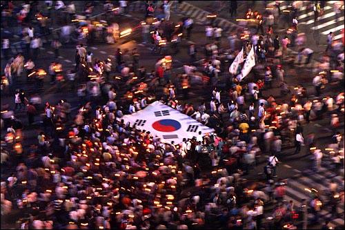 10일 밤 미국산쇠고기 수입 전면 재협상 촉구 및 국민무시 이명박 정권 심판 100만 촛불대행진에 참가한 시민들이 태극기를 펼쳐들고 세종로네거리를 행진하고 있다.