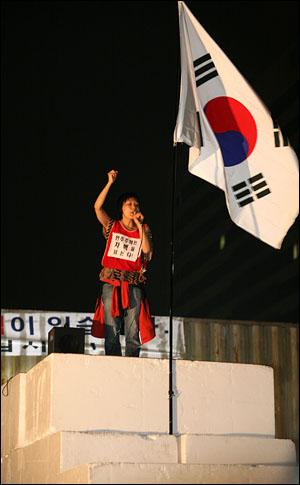 11일 새벽 서울 세종로 사거리 컨테이너 장벽 앞에 스티로폼 블럭으로 계단이 만들어졌고 그 위에서 인권단체 활동가가 시민 자유발언 진행을 위해 연설을 하고 있다.