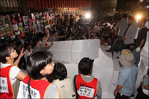 촛불시위대의 청와대 방향 진입을 막기 위해 경찰이 설치한 컨테이너 바리케이트를 넘기 위해 11일 새벽 서울 세종로 사거리에서 일부 시민들이 스티로폼을 옮겨 연단을 만드려고 하자 또 다른 시민들이 '비폭력'을 외치며 만류하고 있다.