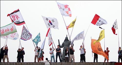 미국산쇠고기 수입 전면 재협상 촉구 및 국민무시 이명박 정권 심판 100만 촛불대행진에 참석했던 학생, 시민들이 11일 새벽 서울 세종로네거리에서 컨테이너 박스 위에 올라가 깃발을 흔들고 있다.