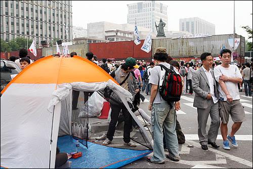 촛불시위대의 청와대 방향 진입을 막기 위해 경찰이 서울 세종로 사거리에 설치한 컨테이너 바리케이트 앞으로 텐트를 치고 밤을 세운 집회 참가자들이 보인다.