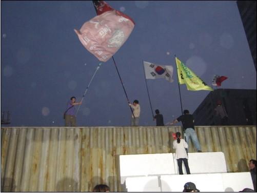 태극기와 단체 소속 깃발을 든 시위참가자들이 '명박산성' 정상에 올라 깃발을 흔들고 있다.
