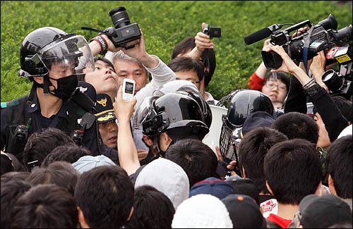 11일 아침 경찰이 서울 세종로 사거리에 모여있던 촛불시위대의 강제해산을 종용하자 디카, 폰카족이 한꺼번에 달려들어 이들을 겨냥하고 있다.