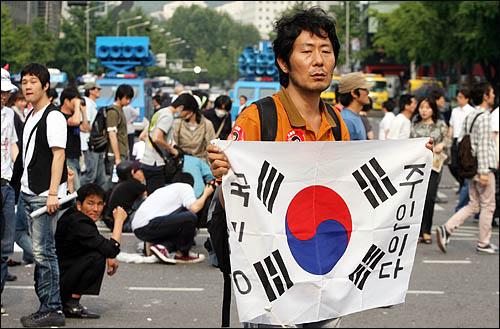 촛불시위대의 청와대 방향 진입을 막기 위해 서울 세종로 사거리에 설치한 컨테이너 바리케이트 철거작업이 11일 오전 진행중인 가운데 한 집회 참가자가 '국민이 주인이다'라고 적은 태극기를 펄럭이고 있다.