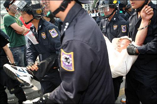 11일 오전 세종로 사거리 차도에서 연좌농성을 하고 잇던 시위대를 경찰이 강제연행하기 시작, 한 노인이 사지를 붙들린채 연행되고 있다.