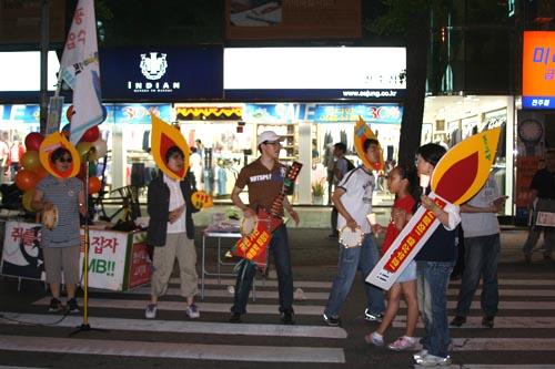 쥐잡는춧불 쥐잡는 촛불을 머리에 쓰고 거리 홍보를 하고 있는 자원봉사자들