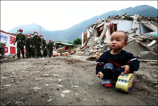 복구대와 아이 과자를 먹고 있는 아이 옆으로 폐허를 복구하기 위한 복구지원대가 지나고 있다