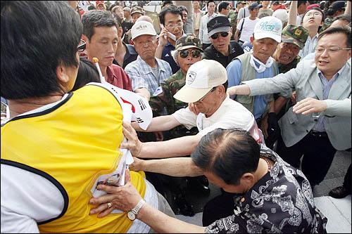13일 반핵반김국민협의회, 대한민국고엽제전우회, 종교인연합회 주최로 열린 국정흔들기 중단 촉구 국민대행진 참가자들이 서울 청계광장에서 미국산 쇠고기 수입에 반대하며 농성중인 시민들을 밀치며 폭행하고 있다.
