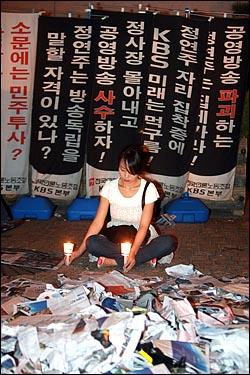 13일 저녁 공영방송 사수를 주장하는 시민들이 여의도 KBS 본사앞에서 촛불집회를 열고 있는 가운데 KBS앞에는 노조가 내건 정연주 사장 퇴진 현수막이 세워져 있다.