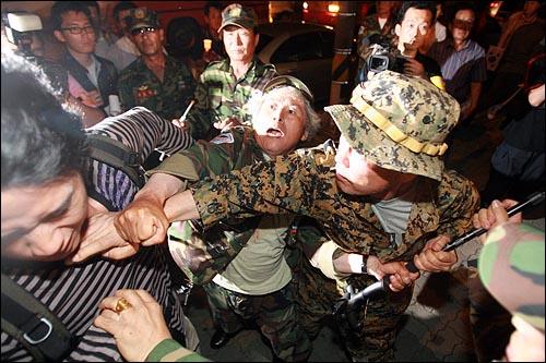 13일 저녁 고엽제전우회 회원들이 여의도 KBS본사앞에서 이명박 정권 공영방송 장악음모 저지를 위한 촛불집회를 열고 있는 시민에게 주먹을 날리고 있다.