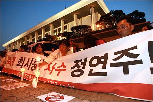 13일 저녁 여의도 KBS앞에서 이명박 정권 공영방송 장악음모 저지를 위한 촛불집회를 열고 있는 시민들이 '퇴진 최시중, 사수 정연주'가 적힌 현수막을 들고 있다.