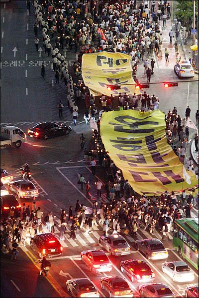 미국산 쇠고기 수입과 대운하 건설에 반대하는 시민들이 17일 저녁 서울시청 앞 광장에서 촛불집회를 연 뒤 '대운하반대' 대형 플래카드를 들고 거리행진을 하고 있다.