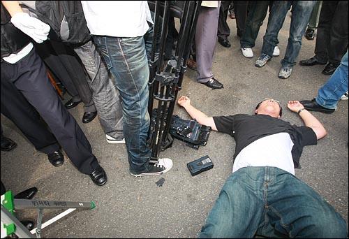 사다리 위에서 취재하던 MBC 카메라 기자가 20일 오후 서울 여의도 MBC 본사 앞에서 국민행동본부와 뉴라이트전국연합 주최로 열린 '광우병선동방송 MBC 규탄' 집회에서 참가자들이 취재방해를 하며 밀쳐 바닥에 넘어져 있다.