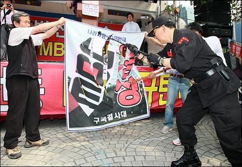 국민행동본부와 뉴라이트전국연합회원들이 20일 오후 서울 여의도 MBC 본사 앞에서 '광우병선동방송 MBC 규탄' 집회에서 광우병 조작 보도하는 MBC 규탄의 현수막을 찢는 퍼포먼스를 하고 있다.