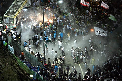 22일 새벽 미국산 쇠고기 재협상 촉구 48시간 릴레이 농성 세째날을 맞아 촛불집중문화제에 참가했던 시민, 학생들이 광화문네거리에 설치된 경찰버스 바리케이트에 밧줄을 묶어 끌어내려 하자 경찰이 소화기를 뿌리고 있다.