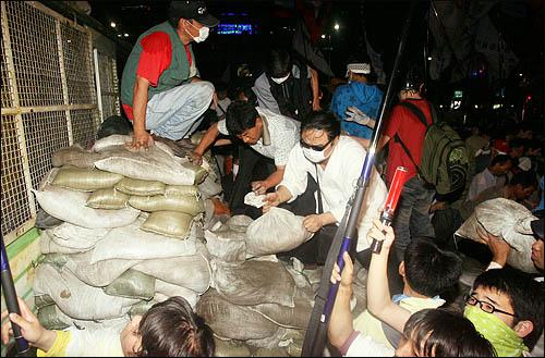 '48시간 비상국민행동' 둘째날인 21일 밤 촛불문화제에 참가한 시민들이 한미 쇠고기 전면 재협상을 요구하며 세종로 사거리에서 청와대로 향하는 길목을 막고 있는 차벽을 넘기 위해 모래주머니 계단을 쌓고 있다.