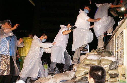 '48시간 비상국민행동' 둘째날인 21일 밤 촛불문화제에 참가한 시민들이 세종로 사거리에서 청와대로 향하는 길목을 막고 있는 차벽앞에 모래주머니 계단을 쌓고 넘어가고 있다.