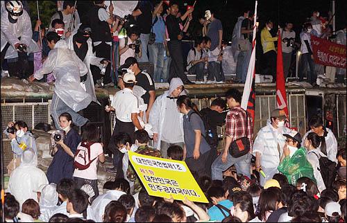 '48시간 비상국민행동' 둘째날인 21일 밤 촛불문화제에 참가한 시민들이 세종로 사거리에서 청와대로 향하는 길목을 막고 있는 차벽앞에 모래주머니 계단을 쌓아 차벽을 넘고 있다.