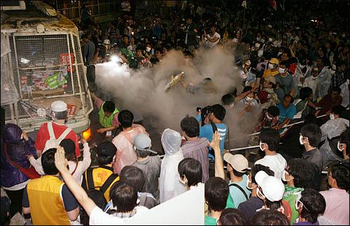 '48시간 비상국민행동' 셋째날인 22일 새벽 미국산 쇠고기 수입에 반대하는 시민들이 세종로 사거리에서 청와대로 향하는 길목을 막고 있는 차벽을 밧줄로 끌어 쓰러뜨리려하자 경찰이 소화분말을 뿌리고 있다.