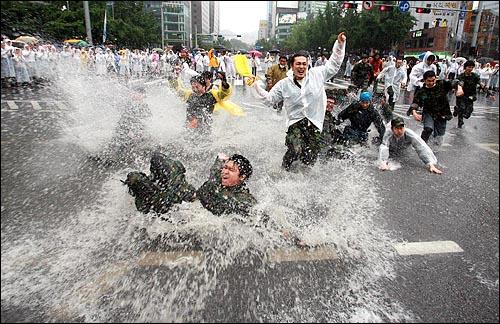 한미 쇠고기 재협상을 촉구하는 48시간 릴레이 농성이 벌어지는 가운데 22일 새벽 수만명의 시민들이 밤새 경찰과 격렬하게 대치했던 세종로 네거리에서 예비군들이 폭우로 생긴 물웅덩이에 뛰어들고 있다.