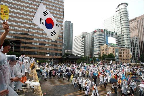 한미 쇠고기 재협상을 촉구하는 48시간 릴레이 농성이 벌어지는 가운데 22일 새벽 서울 세종로네거리에서 밤새 경찰과 격렬하게 대치했던 시민, 학생들이 태극기를 들고 경찰버스 위에 올라가서 노래를 부르고 있다.