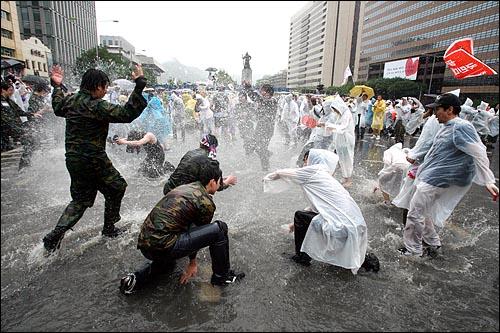 한미 쇠고기 재협상을 촉구하는 48시간 릴레이 농성이 벌어지는 가운데 22일 새벽 서울 세종로네거리에서 밤새워 시위를 벌였던 시민과 예비군들이 폭우로 생긴 물웅덩이에서 물장난을 치고 있다.