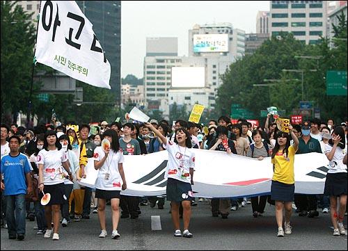 한미 쇠고기 재협상을 촉구하는 48시간 릴레이 농성이 벌어지는 가운데 21일 오후 다음 '아고라' 네티즌과 시민들이 대형태극기를 앞세우고 세종로네거리와 서울시청을 오가며 구호를 외치고 있다.