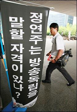KBS 방송 카메라 기자가 23일 오후 서울 여의도 KBS 본관 앞에 정연주 사장 퇴진을 요구하는 만장 옆을 지나고 있다.