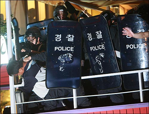 25일 밤 서울 세종로 사거리에서 장관고시 철회와 전면 재협상을 요구하며 시위를 벌이던 한 시민이 광화문 금호아시아나빌딩 뒷편 골몰길로 진입을 시도하다가 경찰들에게 저지되고 있다.