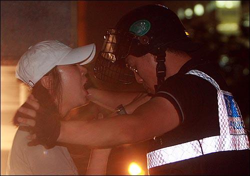 25일 밤 서울 세종로 사거리에서 장관고시 철회와 전면 재협상을 요구하며 시위를 벌이던 한 여성참가자가 광화문 금호아시아나빌딩 뒷편 골몰길로 진입을 시도하다가 경찰에게 저지되고 있다.