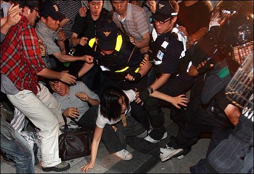 미국산 쇠고기 장관고시에 반대하며 25일 밤 서울 종로구 내수동 서울지방경찰청 부근에서 시위를 벌이던 시민들이 강제연행된 시민들을 태우고 가는 경찰버스를 막고 시위를 벌이다 밀고들어오는 경찰들과 뒤엉켜 넘어지고 있다.