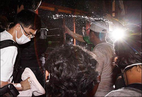 정부가 새로운 미국산 쇠고기 수입 위생조건 고시를 강행키로 한 25일 밤 '촛불' 시민들이 서울 신문로 한글회관 앞에서 청와대로의 진입을 막는 경찰과 대치, 몸싸움을 벌이고 있다.