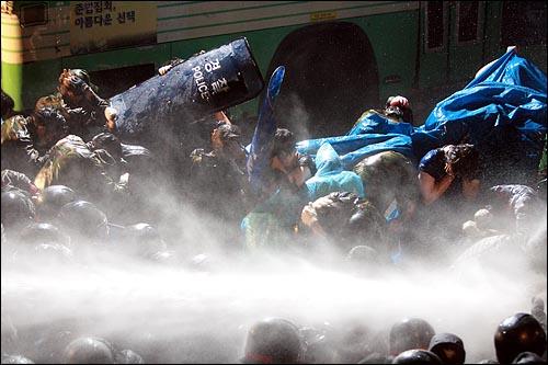 미국산쇠고기 수입위생조건 장관고시에 반대하며 시민, 학생들이 밤샘시위를 벌이는 가운데 26일 새벽 서울 새문안교회 뒤편에서 경찰이 시위대에게 살수차로 물을 뿌리고 있다.