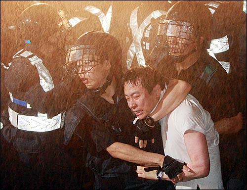 미국산쇠고기 수입위생조건 장관고시에 반대하는 한 시민이 26일 새벽 서울 새문안교회 뒤편에서 밤샘시위를 벌이다가 경찰들에게 강제 연행되고 있다.