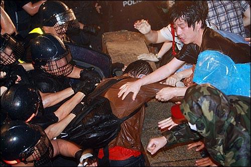미국산쇠고기 수입위생조건 장관고시에 반대하는 한 시민이 26일 새벽 서울 새문안교회 뒤편에서 밤샘시위를 벌이다가 경찰들에게 강제 연행되자 시위 참가자들이 팔을 당기며 저지하고 있다.