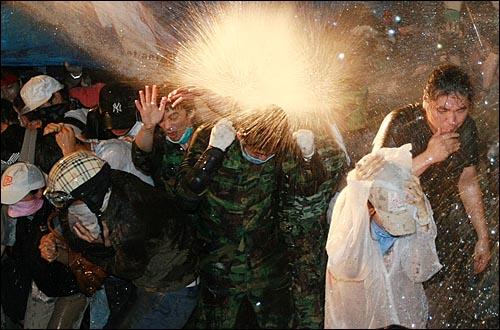 미국산쇠고기 수입위생조건 장관고시에 반대하는 학생과 시민들이 26일 새벽 서울 새문안교회 뒤편에서 밤샘시위를 벌이자 경찰들이 시위대에게 살수차로 물을 뿌리고 있다.