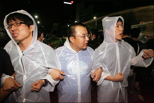 미국산쇠고기 수입위생조건 고시강행에 반대하며 학생과 시민들이 서울 세종로 일대에서 밤샘시위를 벌이는 있는 가운데 26일 새벽 광화문 새문안교회 뒤편에서 경찰이 물대포를 쏘며 시위대를 진압하고 있다.