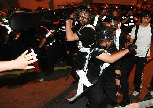 미국산쇠고기 수입위생조건 장관고시에 반대하는 시민, 학생들이 26일 새벽 서울 신문로에서 청와대로 가기 위해 시위를 벌이는 가운데 경찰이 도망치는 시민들을 향해 방패와 주먹을 휘두르고 있다.