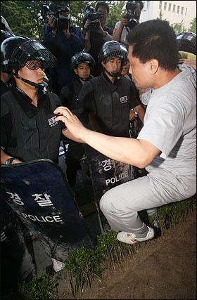 미국산쇠고기 수입위생조건 고시강행에 반대하며 학생과 시민들이 서울 세종로 일대에서 밤샘시위를 벌인 가운데 26일 새벽 경찰이 시위대 강제해산을 시도하며 인도에 올라서자 시민이 항의하며 내려갈 것을 요구하고 있다.