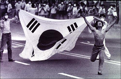 87년 6월 항쟁을 상징하는 사진 한장. 한 청년이 태극기 앞으로 손을 들고 뛰쳐 나가고 있다.