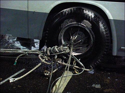 경찰버스. 경찰이 저지선을 지키기 위해 렉카차와 버스를 와이어와 밧줄로 묶어 놓았다.