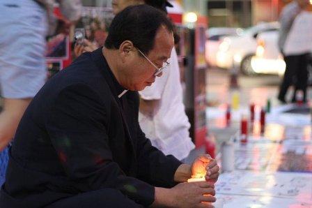 촛불을 밝힌 천주교 이태영 신부