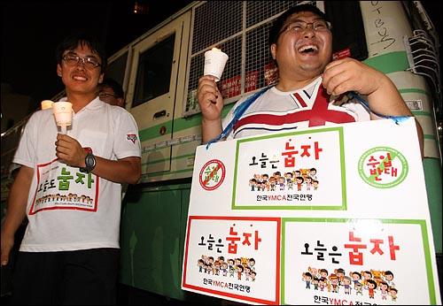 5일 저녁 '국민승리선언 범국민촛불대행진'에 참석한 한국YMCA전국연맹 '눕자' 운동 회원들이 경찰버스앞에서 촛불을 들고 서 있다.
