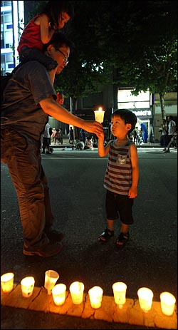 5일 밤 종로거리에서 '국민승리선언 범국민촛불대행진'에 참석했던 한 아빠가 아들에게 촛에 불을 붙여 건네고 있다.