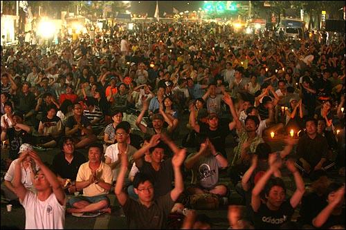 '국민승리선언 범국민촛불대행진'에 참석했던 시민들이 6일 새벽 서울시청앞 광장과 태평로 거리에서 두 팔을 높이 들고 노래에 맞춰 박수를 치고 있다.