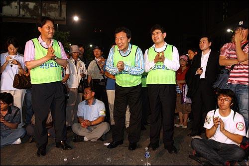 통합민주당 손학규 대표(가운데)가 6일 새벽 '국민승리선언 범국민촛불대행진'에 참여한 뒤 밤샘시위를 벌이는 시민들과 태평로 거리에서 대화를 나누고 있다.