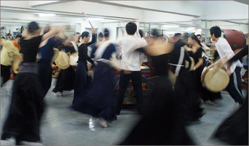 """""""돌아 돌아"""" 2008 베이징올림픽에 국내에서 유일하게 초청받은 '국수호 디딤무용단' 단원들이 큰 북을 중심으로 북을 치며 동그랗게 원을 그리며 돌고 있다."""