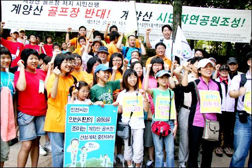 인천 시민들과 시민단체 회원들이 계양산 골프장 조성 사업을 반대하는 산행에 앞서 구호를 외치고 있다