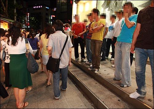 9일 저녁 서울 종로 보신각앞에서 광우병국민대책회의 주최로 열린 제94차 촛불문화제에 참석했던 시민들이 거리시위에 나선 가운데, 탑골공원 네거리 한 옷가게 앞에 사복경찰 수십명이 배치되어 시민들을 감시하고 있다.