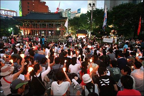 9일 저녁 서울 종로 보신각앞에서 광우병국민대책회의 주최로 열린 제94차 촛불문화제에 참석한 시민들이 촛불을 높이들고 '이명박 퇴진'  구호를 외치고 있다.